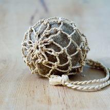 Bourse, filet noué au «nœud des lacustres», en feuilles de palmier-raphia, contenant une boule naturelle de feutre de feuilles de posidonie de Méditerranée.